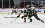 Anaheim's Ben Hutton (7) and the Wild's Nick Bonino (13) go after the puck during the second period on March 22