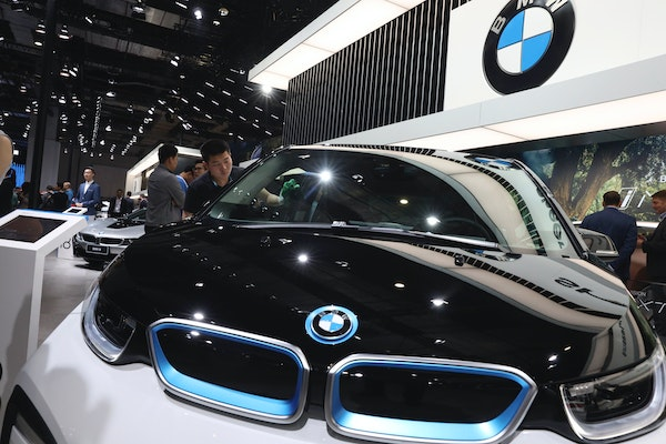 In this April 17, 2019 file photo, a worker cleans an electric vehicle at the BMW booth during the Auto Shanghai 2019 show in Shanghai. Automakers BMW