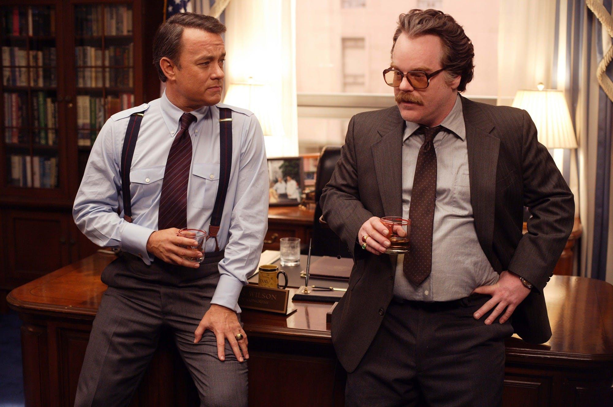 Tom Hanks as Charlie Wilson and Philip Seymour Hoffman as Gust Avrakotos.
