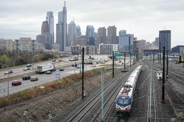 An Amtrak train departs 30th Street Station moving parallel to motor vehicle traffic on Interstate 76 in Philadelphia.