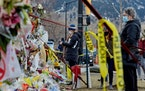 Mourners pay respects at a makeshift memorial for the victims of a shooting in Boulder, Colo.