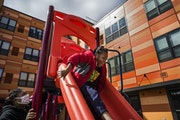 At the playground at her mother's apartment complex, Janesha Anderson watches her son Jermel, 7, play. She has struggled to meet the cumbersome pape