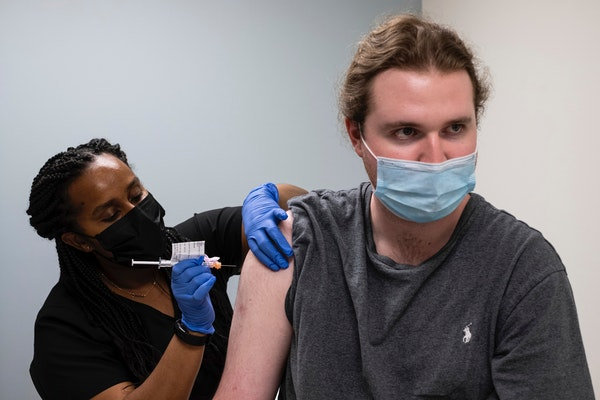 Cole Smith receives a Moderna variant vaccine shot from clinical research nurse Tigisty Girmay at Emory University's Hope Clinic, on Wednesday after
