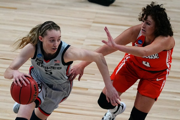 UConn guard Paige Bueckers (5) drives under pressure from Syracuse guard Tiana Mangakahia (4)  during an NCAA regional game.