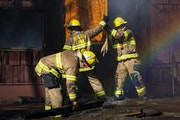 FILE-Two Duluth firefighters removed wooden boards and debris from a doorway where smoke was pouring out in the former Paul Robeson Ballroom and Kozy