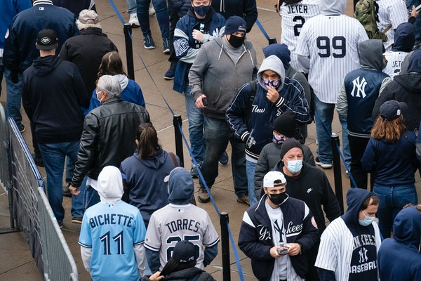 Spectators wait on a security line outside Yankee Stadium before an opening day baseball game against the Toronto Blue Jays, Thursday, April 1, 2021,