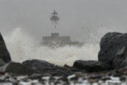 FILE-Snow falls as waves crash onto the shore in Canal Park in Duluth in 2019. The City Council is poised to delcare a climate emergency in the face o