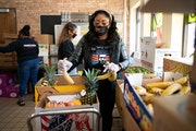 Bridgett Floyd and members of Visual Black Justice helped pack produce boxes for families at a Salvation Army location on Lake Street on Thursday, Apr