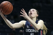 FILE - UConn guard Paige Bueckers (5) shoots against Xavier during the first half of an NCAA college basketball game in Cincinnati, in this Saturday,