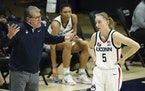 Connecticut head coach Geno Auriemma, left, talks with guard Paige Bueckers (5) during a break in the first quarter against Marquette during an NCAA c