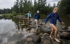 People walk across the Mississippi River at Itasca State Park.