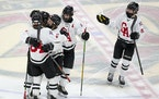 Gentry Academy players swarm defender Isaiah Norlin (64) after he scored a goal to give them a 2-0 lead in the second period. ]