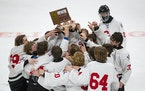 Gentry Academy players raised their trophy after winning the boys' hockey Class 1A state championship
