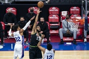Timberwolves' Karl-Anthony Towns shoots between Philadelphia 76ers' Tobias Harris, right, and Matisse Thybulle during the first half