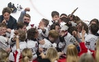 Eden Prairie jumped into the glass in front of their fan section after winning the Group AA boy's hockey state championship. ]