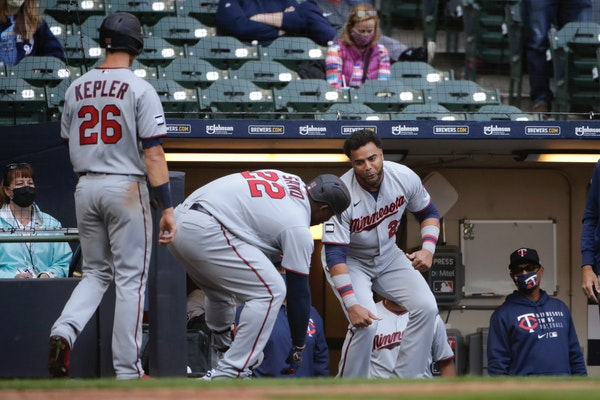 Miguel Sano (22) is congratulated by teammates in the dugout after hitting a two-run home run.