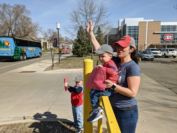 Heather Mayer of St. Cloud and sons Finley, 5, and Emmett, 2, send off the St. Cloud State men's hockey team as it departs for the Frozen Four on Mo