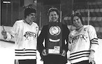Don Brose holds Minnesota State's 1980 NCAA Division II men's hockey trophy with captain Steve Forliti (left) and Steve Loomis (right).