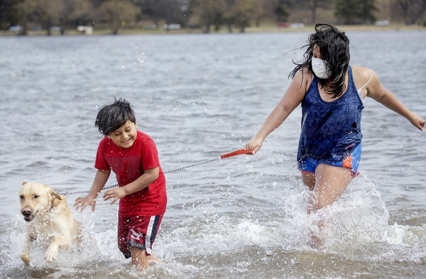 Owen Montero, 7, left, and Dulce Pereanez, 11, and their dog Bruno joined many who flocked to Lake Nokomis on Monday. Pereanez said the water was cold