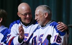 """In this Feb. 21, 2015, photo, Jack O'Callahan, left, and Mark Pavelich of the 1980 U.S. ice hockey team talk during a """"Relive the Miracle"""" reuni"""