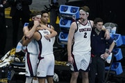 Gonzaga forward Corey Kispert (24) hugs Jalen Suggs (1) as Gonzaga forward Drew Timme (2) looks on at the end of the championship game.