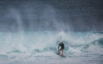 Rivan Rock Rosskopf surfs the Banzai Pipeline while wearing a surfing helmet, in Haleiwa, Hawaii. Young surfers on the North Shore of Oahu are embraci