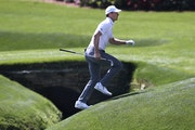 Jordan Spieth runs across the tributary to Rae's Creek to the 13th green during his practice round for the Masters at Augusta National Golf Club.