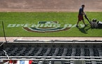 Grounds crew members prepare Target Field for the April 8 home opener Tuesday in Minneapolis.        ]                 DAVID JOLES • david.joles@sta