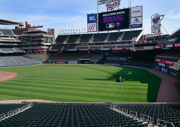 Grounds crew members prepare Target Field for the April 8 home opener