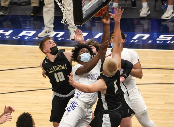 Caledonia's Jackson Koepke (10) and Austin Klug (3) defend Minneapolis North's Mario Sanders (1) under the basket in the Class 2A semifinal Wednes
