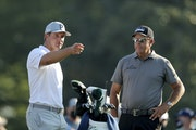 Bryson DeChambeau, left, talks with Phil Mickelson on the 10th tee during a practice round for the Masters