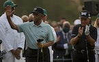Lee Elder waves with Gary Player before the ceremonial first tee the first round of the Masters.
