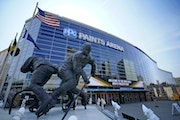 A statue of Pittsburgh Penguins Hockey Hall of Fame center Mario Lemieux, left, stands in front of the PPG Paints Arena, site of the Frozen Four.