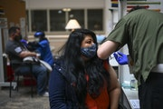 Matt Brenner, a temporary nurse with the Minneapolis VA, administered a dose of the Pfizer-BioNTech COVID-19 vaccine to Pamela George, 34, of Rogers,