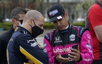 Tony Kanaan, of Brazil, left foreground, talks with Helio Castroneves, of Brazil, before testing at the Indianapolis Motor Speedway