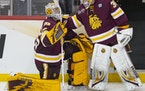 Backup UMD goaltender Ben Patt (36) comforted starting goaltender Zach Stejskal (35) after he gave up a goal to University of Massachusetts in overtim