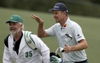 Justin Rose and his caddie David Clark react to his second shot on the eighteenth hole during the first round of the Masters.