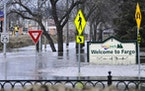 In this April 8, 2011 file photo, a welcome sign for Fargo, N.D., sits in the rising floodwaters of the Red River as a flood engineer for the U.S. Arm
