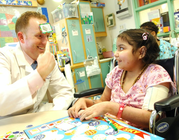 M Health Fairview pediatrician Michael Pitt uses humor and tricks to help his young patients feel less nervous during exams. caption