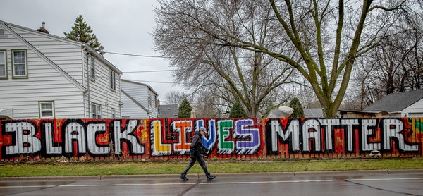 A man walks on the road Friday near a fence that is at the center of controversy where a couple have been asked by the city of West St. Paul to paint