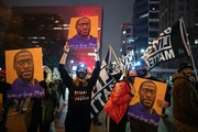 Members of Visual Black justice held signs together. ] Mark Vancleave – About a hundred protesters gathered for a late-evening demonstration against