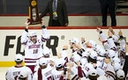 Massachusetts forward Jake Gaudet yelled in celebration while holding the NCAA men's hockey national championship trophy
