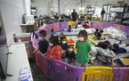 FILE - In this March 30, 2021, file photo, young unaccompanied migrants, from ages 3 to 9, watch television inside a playpen at the U.S. Customs and B