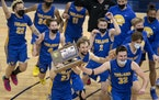 Camden Heide (23), Drew Berkland (15), Carter Bjerke (32) and Wayzata teammates celebrated with championship trophy.