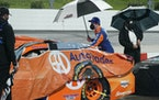 Brad Keselowski helps to cover his car during a rain delay in the NASCAR Cup Series race at Martinsville