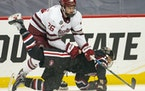 Massachusetts Minutemen defenseman Colin Felix (26) knocked St. Cloud State Huskies forward Jami Krannila (13) to the ice in the first period.
