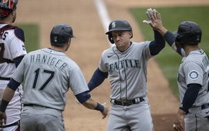 Seattle third baseman Kyle Seager (15) celebrated his three-run homer in the ninth inning with Mitch Haniger, left, and Ty France.