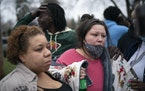 Friends and family comforted Katie Wright, right, while she spoke briefly to news media near where her son, Daunte Wright, 20, was shot and killed by