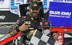 Martin Truex Jr. celebrated with a fan after winning Sunday's rain-delayed NASCAR race at Martinsville Speedway.