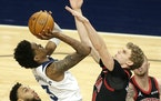 Minnesota Timberwolves forward Jaden McDaniels (3) shoots on Chicago Bulls forward Lauri Markkanen (24) Chicago Bulls center Nikola Vucevic (9) on the
